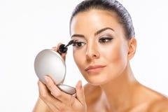 Femme appliquant le mascara sur des cils Photos libres de droits