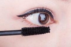 femme appliquant le mascara sur ses cils photo libre de droits