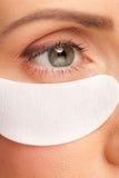 Femme appliquant le masque d'oeil de gel Image stock
