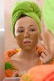 Femme appliquant le masque facial à partir de l'argile brun Photo stock