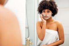 Femme appliquant le masque facial images stock