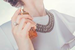 Femme appliquant le parfum sur son cou Image stock