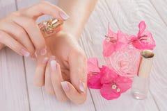 Femme appliquant le parfum sur son poignet Photographie stock libre de droits