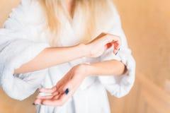 Femme appliquant le produit de beauté pour des mains, soins de la peau Image stock