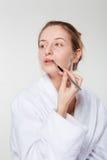 Femme appliquant le rouge à lèvres avec un applicateur images libres de droits