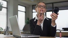 Femme appliquant le rouge à lèvres dans le lieu de travail, le concept de la robe et le code d'aspect banque de vidéos