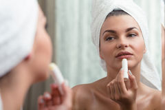 Femme appliquant le rouge à lèvres protecteur Images stock