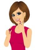 Femme appliquant le rouge à lèvres rose sur des lèvres illustration libre de droits