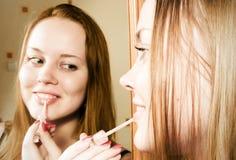 Femme appliquant le rouge à lievres devant le miroir Photos stock