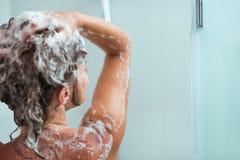 Femme appliquant le shampooing dans la douche Images libres de droits