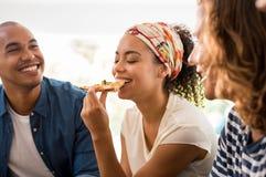Femme appréciant la pizza avec des amis Photos libres de droits