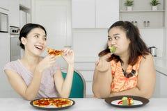 Femme appréciant la pizza et raillant son ami Photos libres de droits