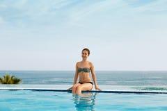 Femme appréciant la relaxation dans la piscine et le regard image stock