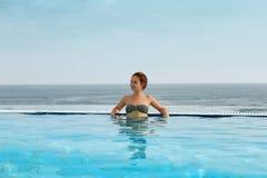 Femme appréciant la relaxation dans la piscine et le regard photo libre de droits