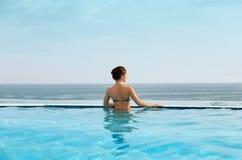 Femme appréciant la relaxation dans la piscine et le regard photo stock