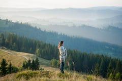 Femme appréciant le beau paysage avec la brume de matin au-dessus des montagnes Image libre de droits