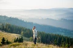 Femme appréciant le beau paysage avec la brume de matin au-dessus des montagnes Photo stock