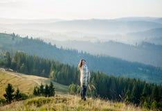 Femme appréciant le beau paysage avec la brume de matin au-dessus des montagnes Photographie stock