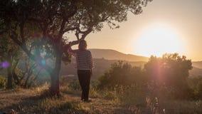Femme appréciant le coucher du soleil image stock