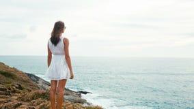Femme appréciant le coucher du soleil au bord d'une falaise près de l'océan banque de vidéos