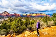 Femme appréciant le coucher du soleil au-dessus de la montagne de tonnerre et d'autres montagnes rouges de roche entourant la vil image stock
