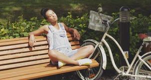 Femme appréciant le soleil sur le banc en parc image stock