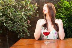 Femme appréciant le temps sur la terrasse avec le verre de vin Photographie stock libre de droits