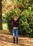 Femme appréciant les feuilles de chute image stock