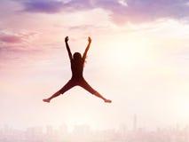 Femme appréciant sauter tout en refroidissant sur la ville et le ciel Images stock