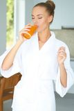 Femme appréciant un verre de jus d'orange photos stock