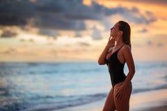 Femme appr?ciant le beau coucher du soleil sur la plage image libre de droits