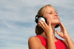Femme appréciant la musique Photographie stock