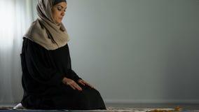 Femme arabe à genoux se prosternant sur la couverture de prière islamique, culte religieux, foi banque de vidéos