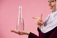 Femme arabe dans le doigt de points de hijab à la bouteille image stock