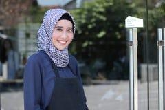 Femme arabe de sourire de Hijab avec le tablier posant devant la porte en verre faisant bon accueil à un costume photographie stock libre de droits
