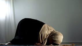Femme arabe ? genoux se prosternant sur la couverture de pri?re islamique, culte religieux, foi photo libre de droits