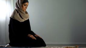 Femme arabe religieuse s'asseyant sur la couverture de prière islamique, culte religieux, foi image stock
