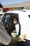 Femme arrêtée s'asseyant dans la voiture de police image stock
