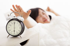 Femme arrêtant le réveil sur le lit photo stock