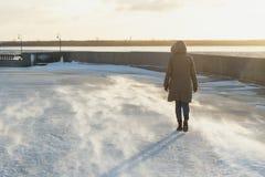 Femme arrière de vue dans une veste d'hiver avec un capot allant sur le remblai d'une rivière de congélation en hiver blizzard photos stock