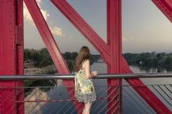 Femme arrière se tenant sur un pont rouge au-dessus de l'Èbre, Espagne Photographie stock libre de droits