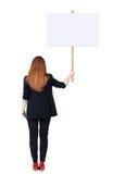 Femme arrière d'affaires de vue montrant le panneau de signe Image libre de droits