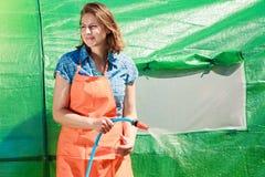 Femme arrosant le jardin avec le tuyau Image libre de droits