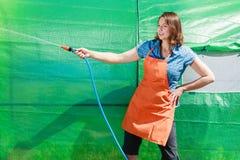 Femme arrosant le jardin avec le tuyau photo stock