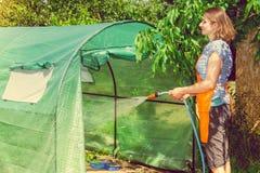 Femme arrosant le jardin avec le tuyau photographie stock libre de droits