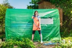 Femme arrosant le jardin avec le tuyau images stock