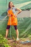 Femme arrosant le jardin avec le tuyau photos libres de droits