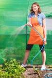 Femme arrosant le jardin avec le tuyau photo libre de droits