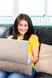 Femme asiatique à l'aide de l'ordinateur portable sur le divan Photos libres de droits