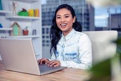 Femme asiatique à l'aide de l'ordinateur portatif image stock